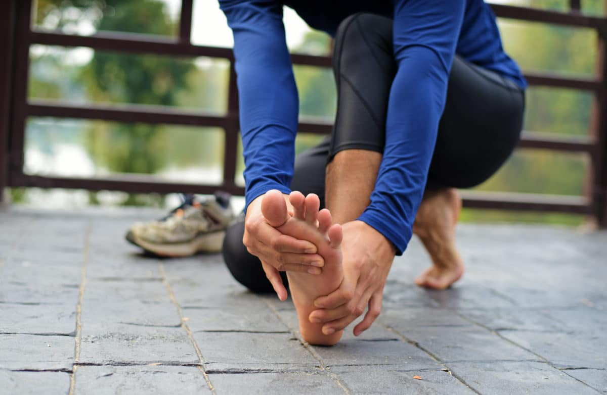Runner's Guide to Prevent Pain runner holding her foot with painful stress fracture