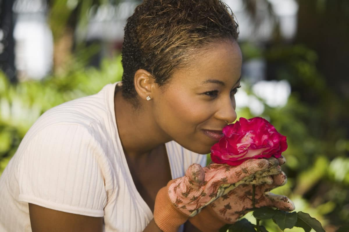 Pain-Friendly Hobbies woman smelling flower in her garden