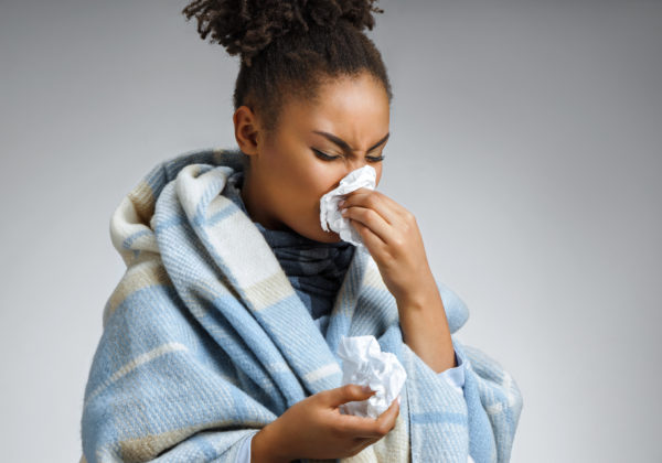 Throat Pain and Headaches woman sneezing with common cold