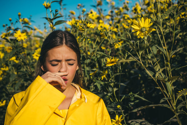 Throat Pain and Headaches woman sneezing with sinus infection
