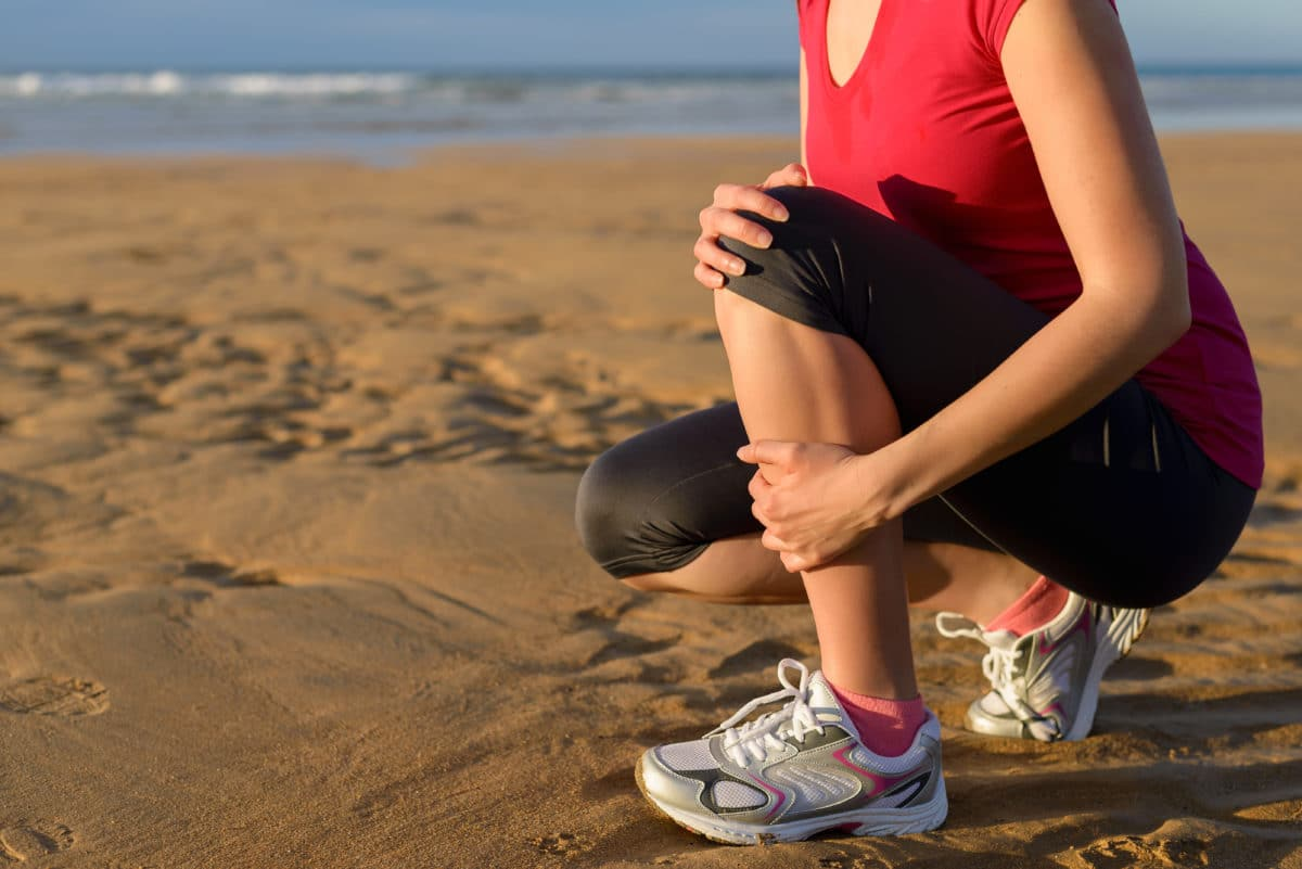 Runner's Guide to Prevent Pain runner with painful shin splints on the beach
