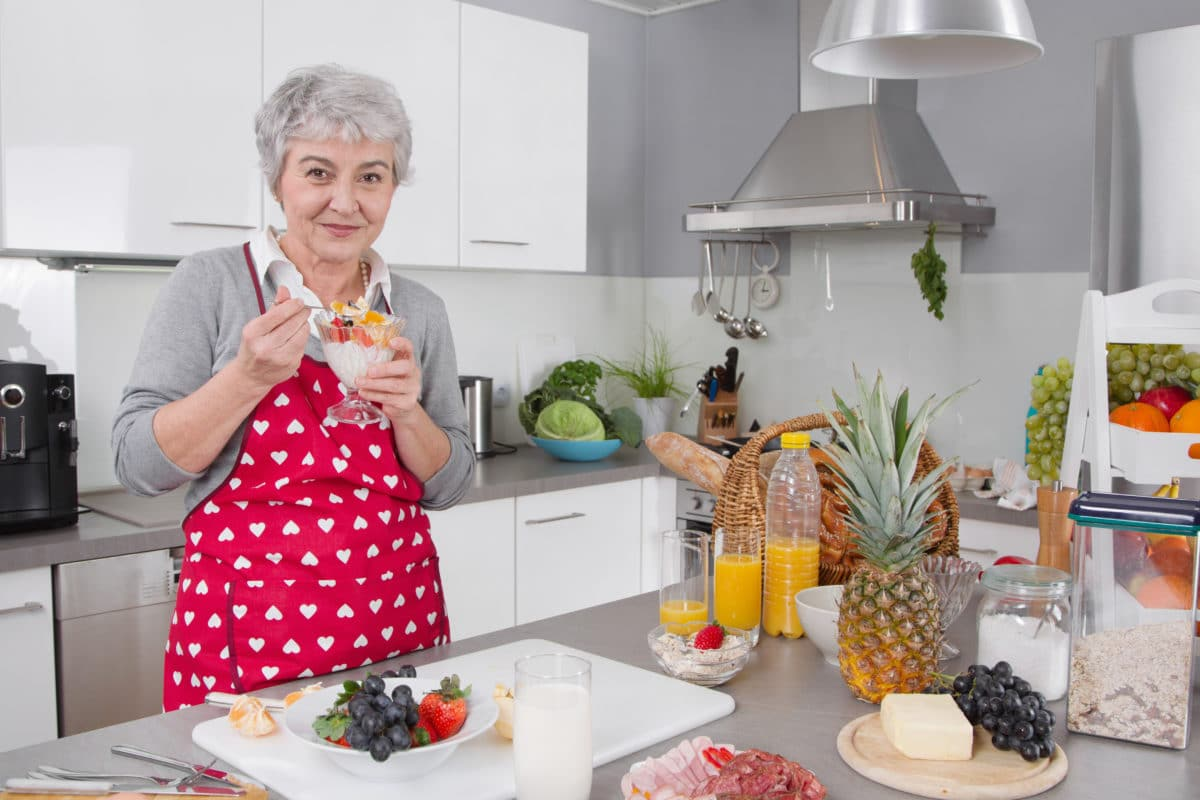 senior woman eating healthy foods in kitchen
