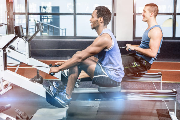 Two men on rowing machines in gym fitness trend