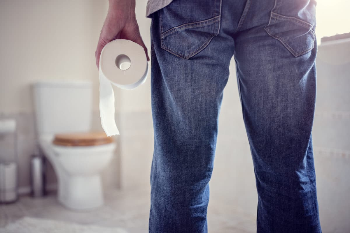 abdominal pain and bloat man with abdominal pain holding toilet paper in bathroom