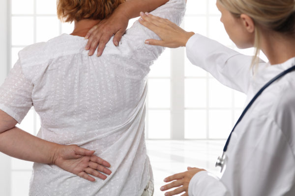 Relieve Work-Related Shoulder Pain doctor treating patient with shoulder pain