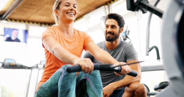 Woman and man on rowing machines fitness trend